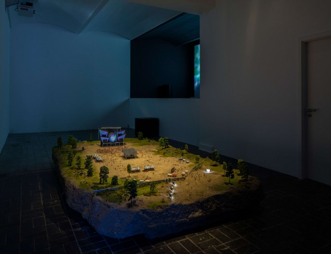 Anne de Vries: Installation view, Photo: Timo Ohler. From left to right: Oblivion, 2016,  Diorama in a scale of 1:87; sand, stones, wood, plastic, aluminum, paint, PVA, styrofoam, miniature advertisement cam­paign, miniature graffiti, miniature truss system, miniature LED projector, miniature Hi-Fi system, Courtesy Anne de Vries /Critical Mass: Pure Immanence, 2015, Full HD video, color, sound, loop, 14′, video edit, lyrics, and musical arrangement Anne de Vries, Q-Dance, Music Phill Niblock, Thomas Ankersmit, Pye Corner Audio, Incredible String Band, Nils Frahm, Aqua Dome and others, Courtesy Anne de Vries